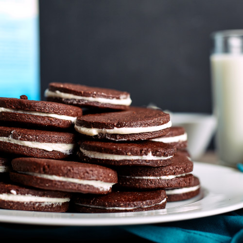 Chocolate sandwich cookies with cream filling on wood background. Glass of milk at background